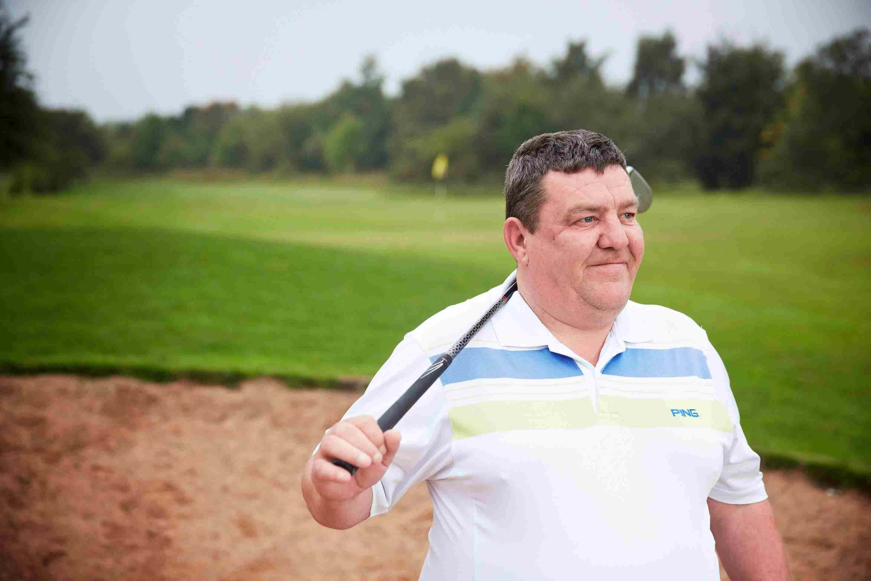 Serious injury client, Ian, is on a golf course with a golf club over his shoulder.