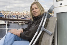 female sat in front of a harbour with crutches by her side