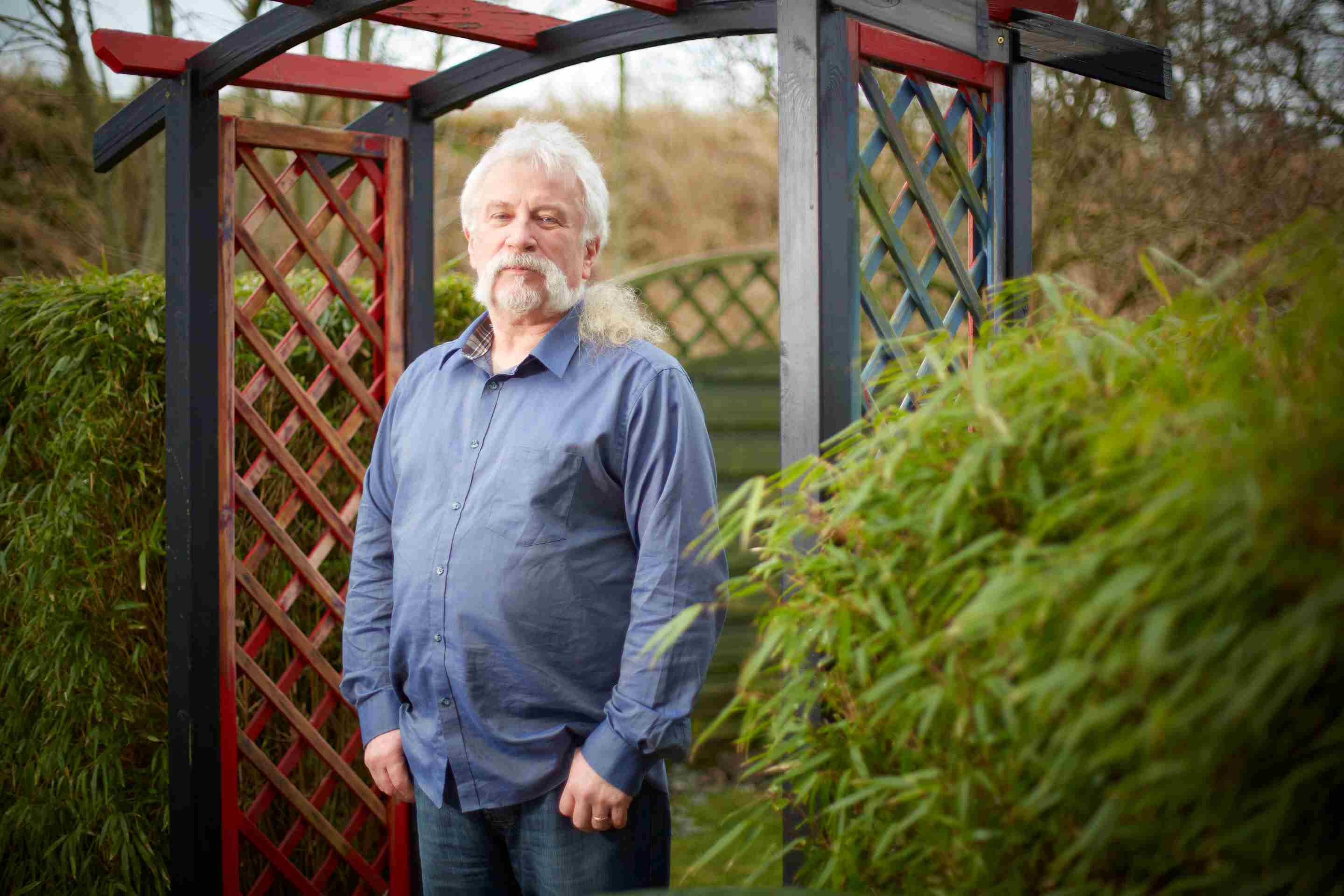 A man in a blue shirt with white hair stands in a garden archway, hands in pockets