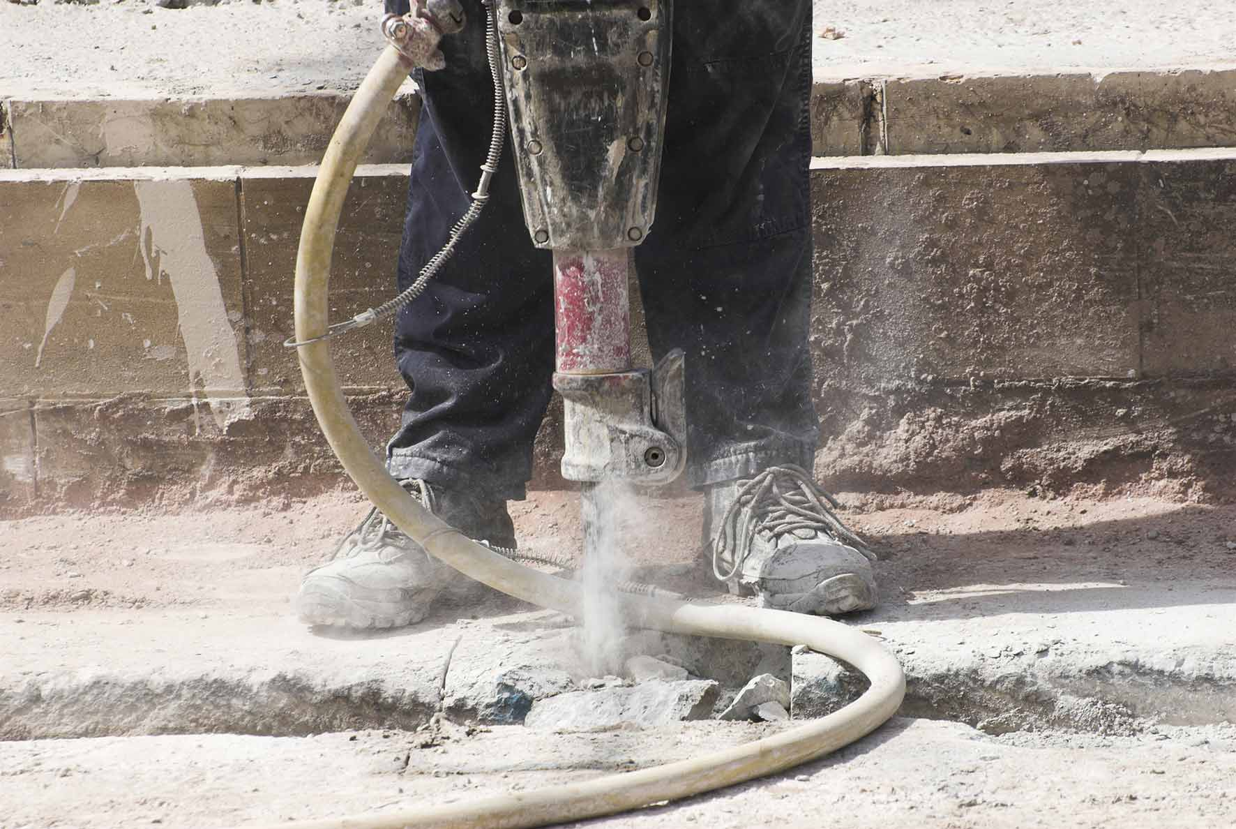 labourer using an electric drill to drill through pavement causing dust