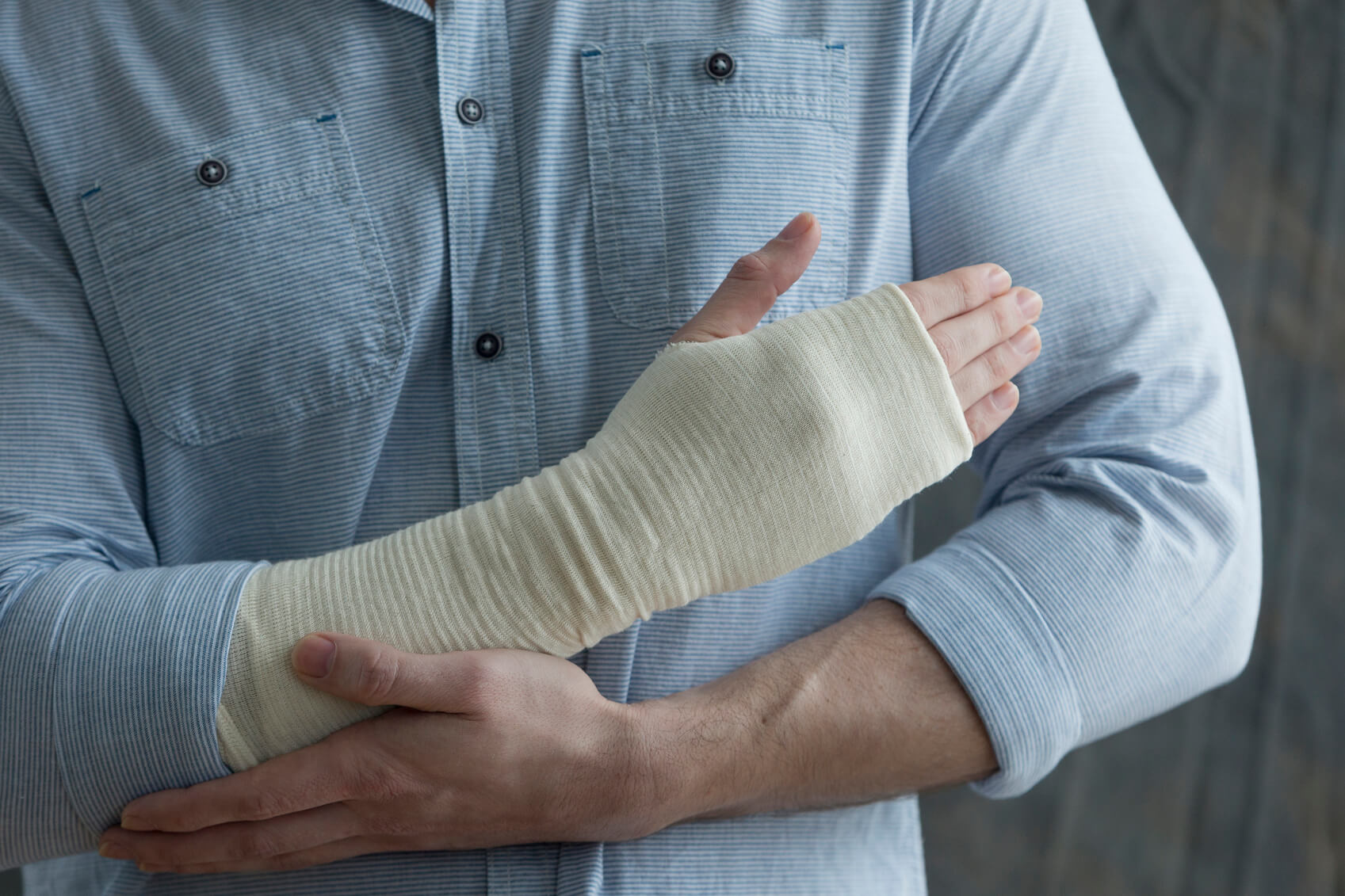 A man holds his bandaged wrist