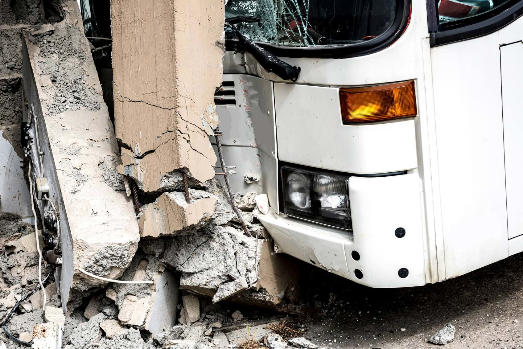 close up of a bus which has crashed into a wall both are damaged severely