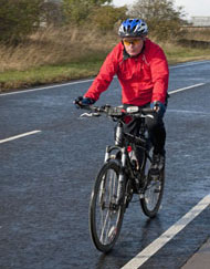 cyclist riding on the road wearing red jacket and blue helmet