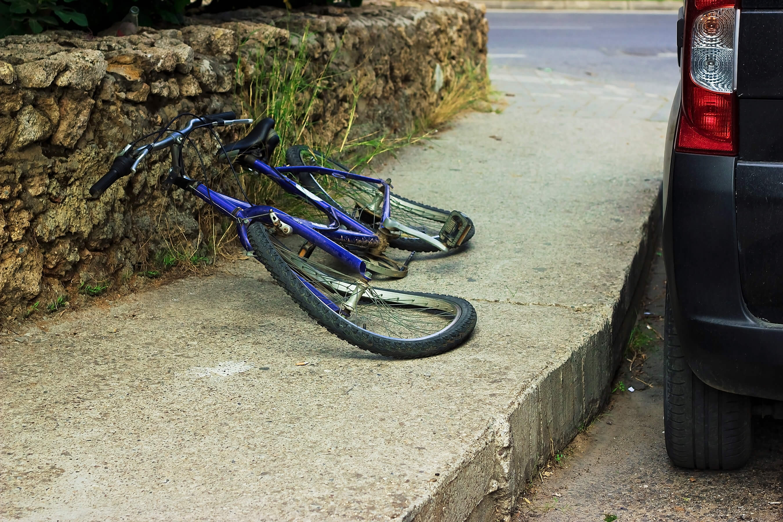 blue bicycle lying damaged on the pavement next to a black van