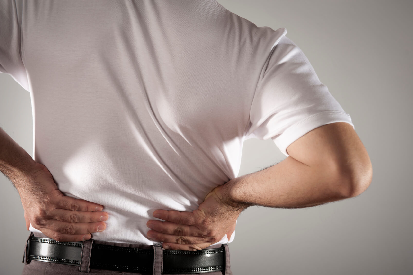 male in white t-shirt clutching his back in pain