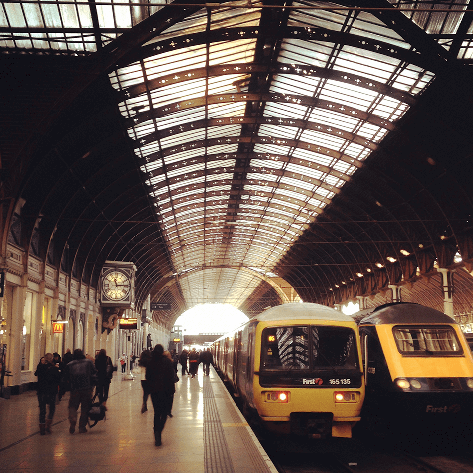 front facing shot of two stationary trains at  a uk station with passengers on the platform