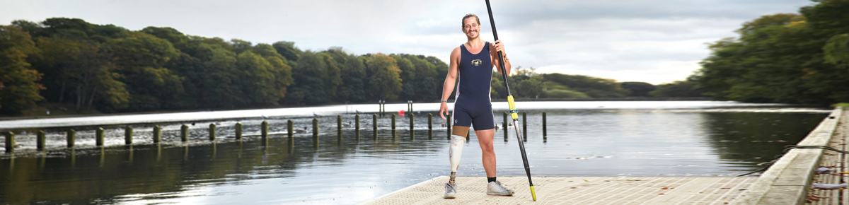 Matthew Roche stands with a false limb, smiling at the camera with water and trees behind him.