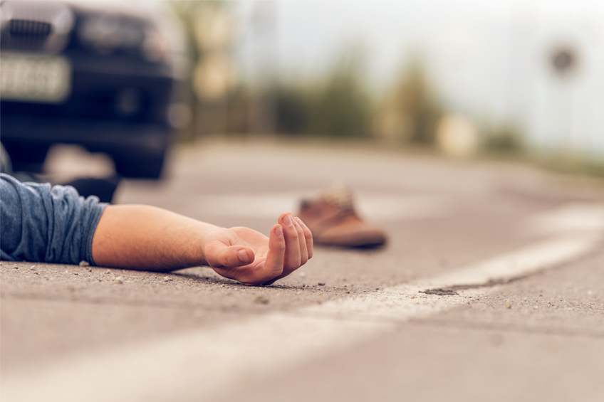 arm of a man lying face up on a road shoe and car blurred in background