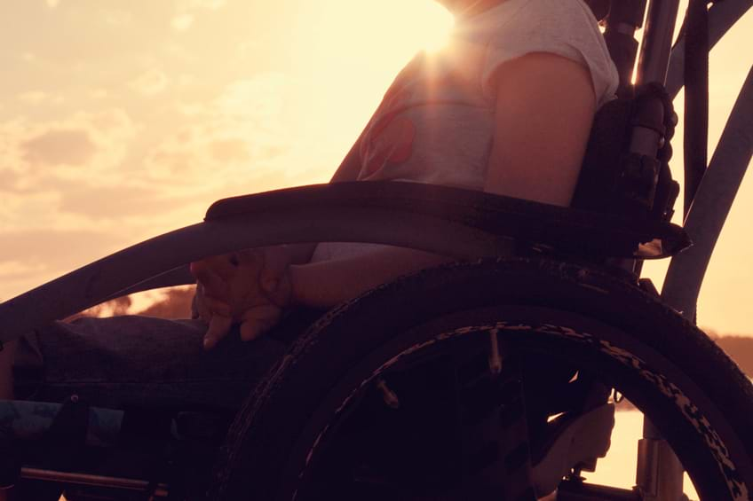 sunset shot of a child's torso and legs sat in a wheelchair