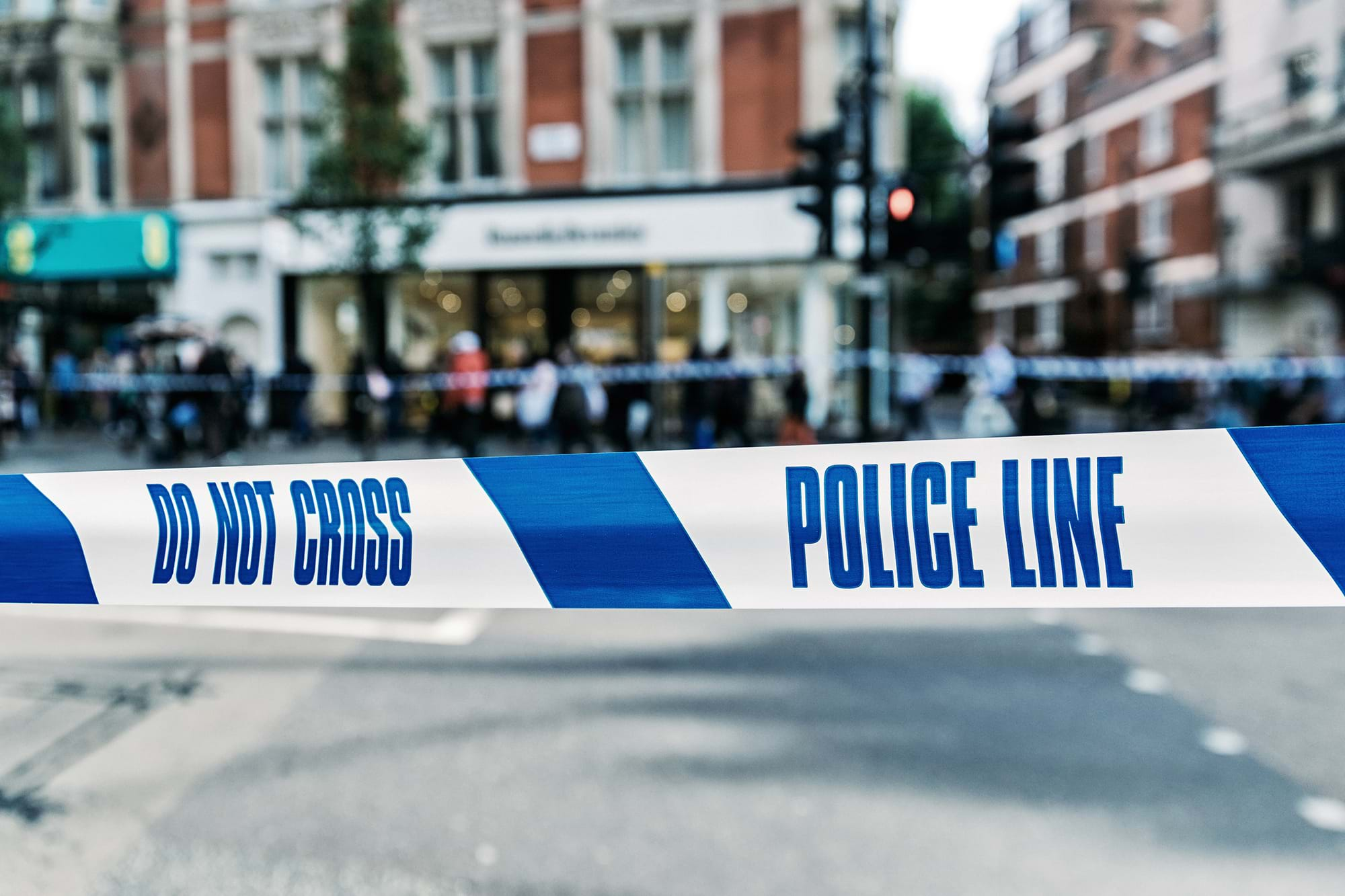 Police 'do not cross' tape on a busy highstreet